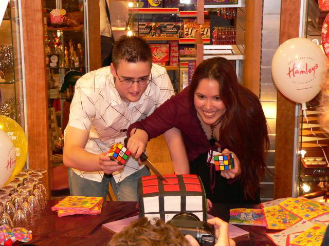 Dan and Jasmine cutting the very cool Rubik's Cube cake at Hamleys