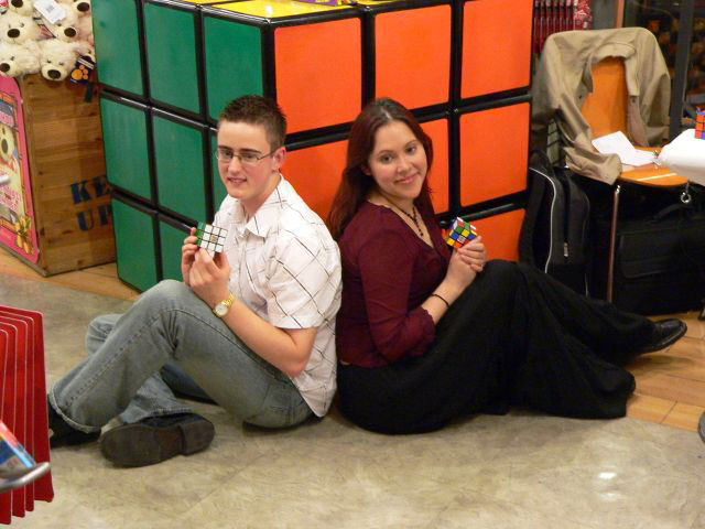 Jasmine and Dan posing in front of the enormous Rubik's Cube for the photographer